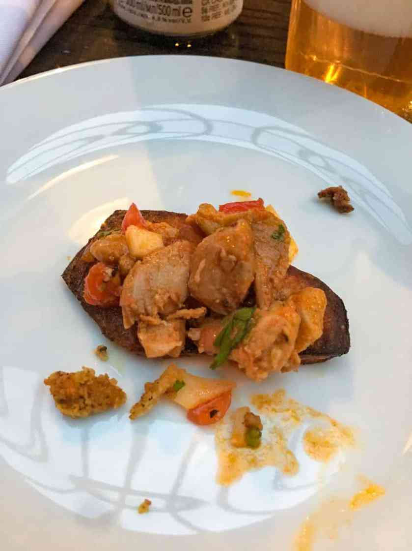 Course 1 Chef Kris Schoenberger: House rubbed butter and cream roasted potatoes topped with tomato bruschetta, balsamic glaze, and fried chicken skins