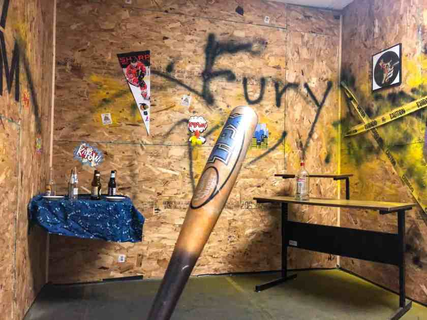 A single bat in a room with graffiti on the walls