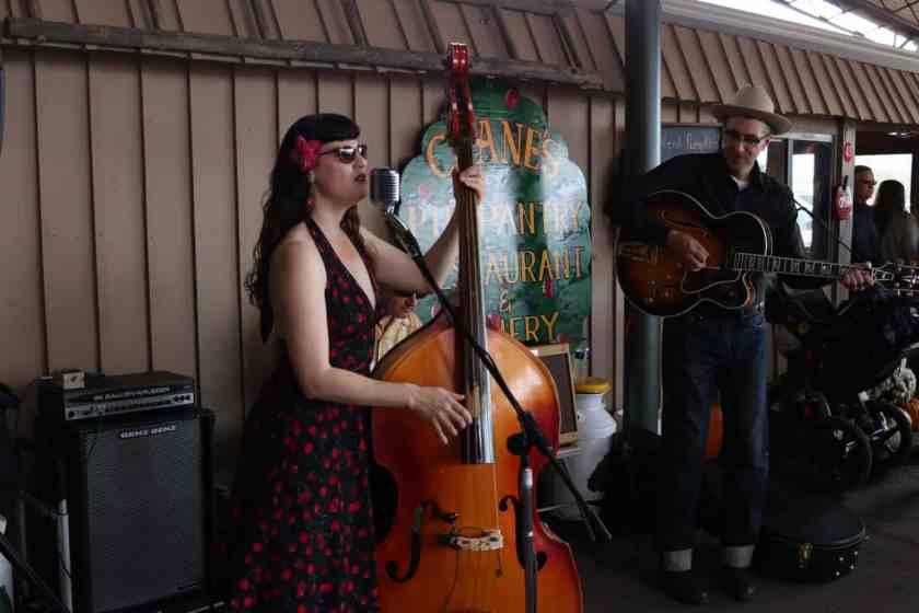 Woman playing an upright bass on patio while singing at Crane's Restaurant