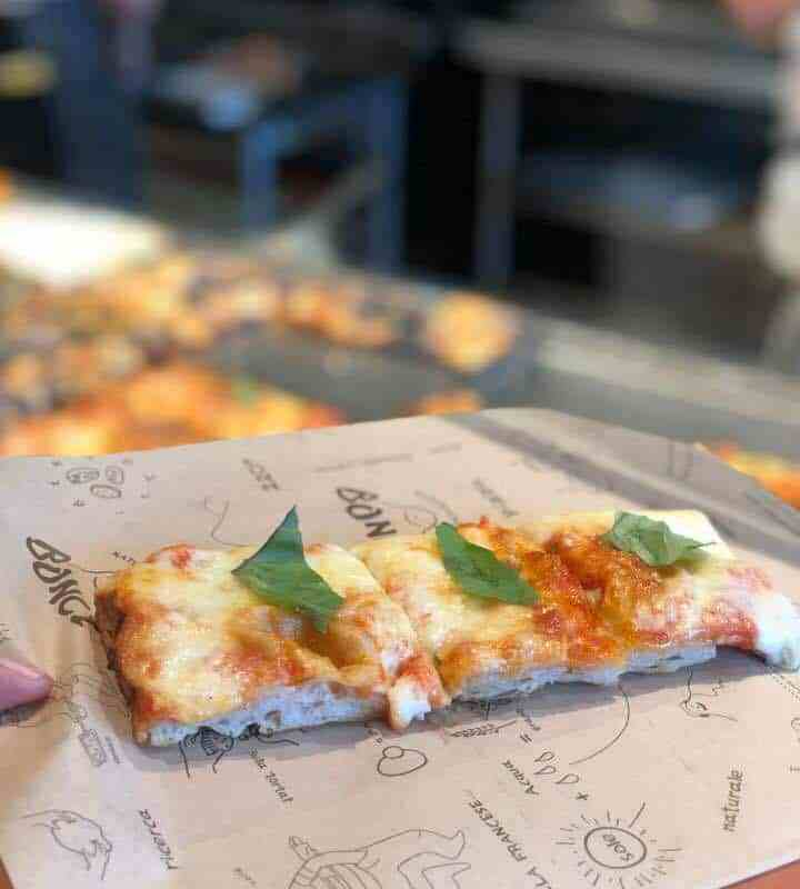 Thin crust pizza topped with cheese, tomato, and basil