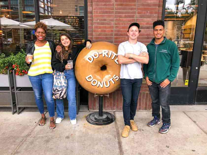 4 people posing next to a giant donut statue