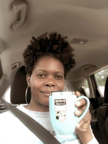 Woman smiling at camera holding a mug of coffee on a road trip to Hamilton County, Indiana
