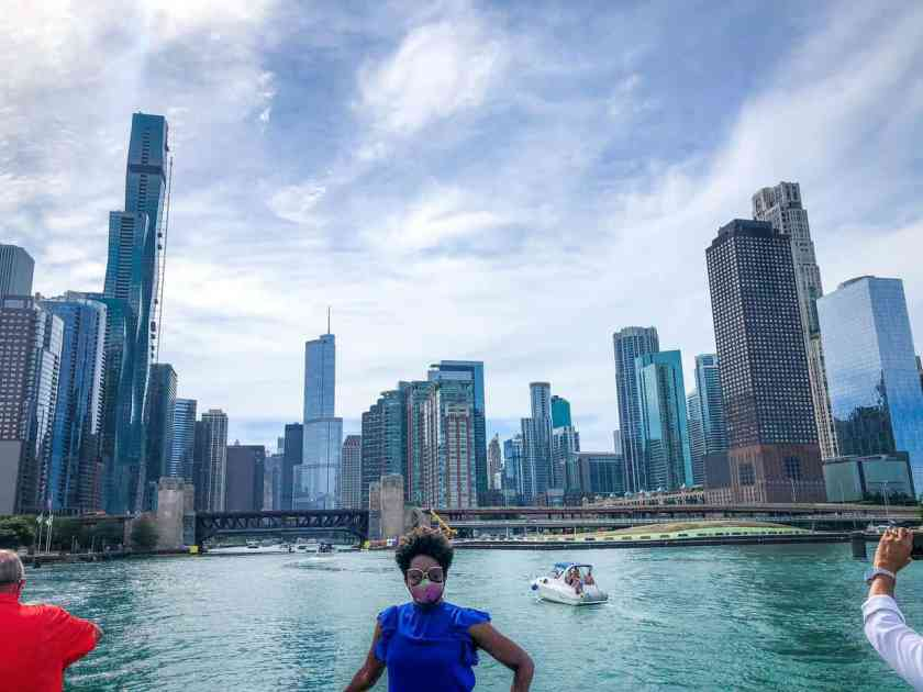 Woman standing on boat with cityscape backdrop on Chicago tour