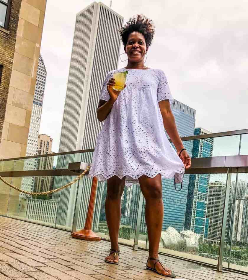 Woman holding cocktail smiling at camera during Chicago Staycation