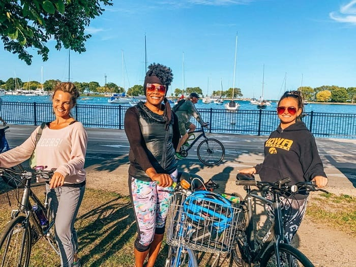 Group of smiling women standing next to their bikes