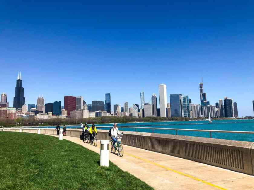 people biking along Chicago's lakefront with skyscraper buildings in the background