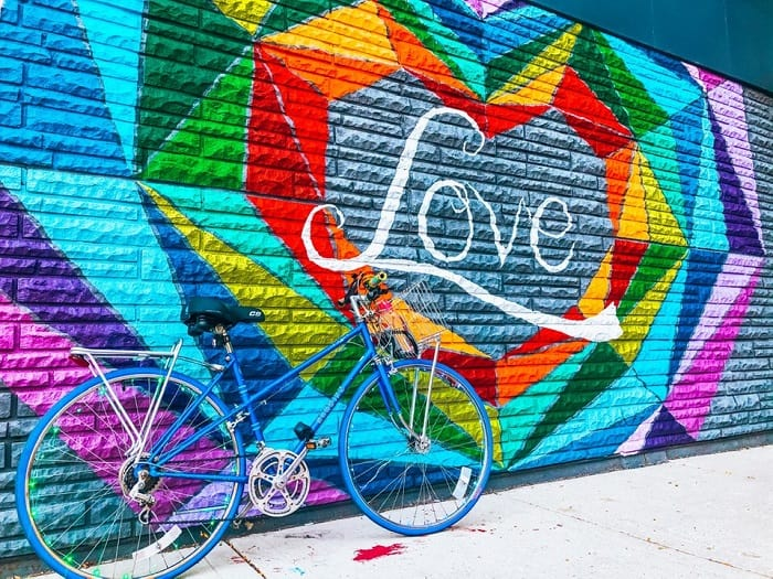 Bike leaning on a rainbow mural with Love written in the middle