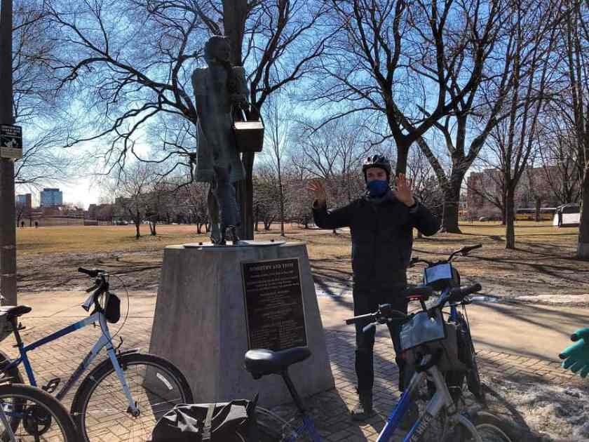 A guide standing next to a statue of Dorothy from the Wizard of Oz in Oz Park during a guided chicago bike tour