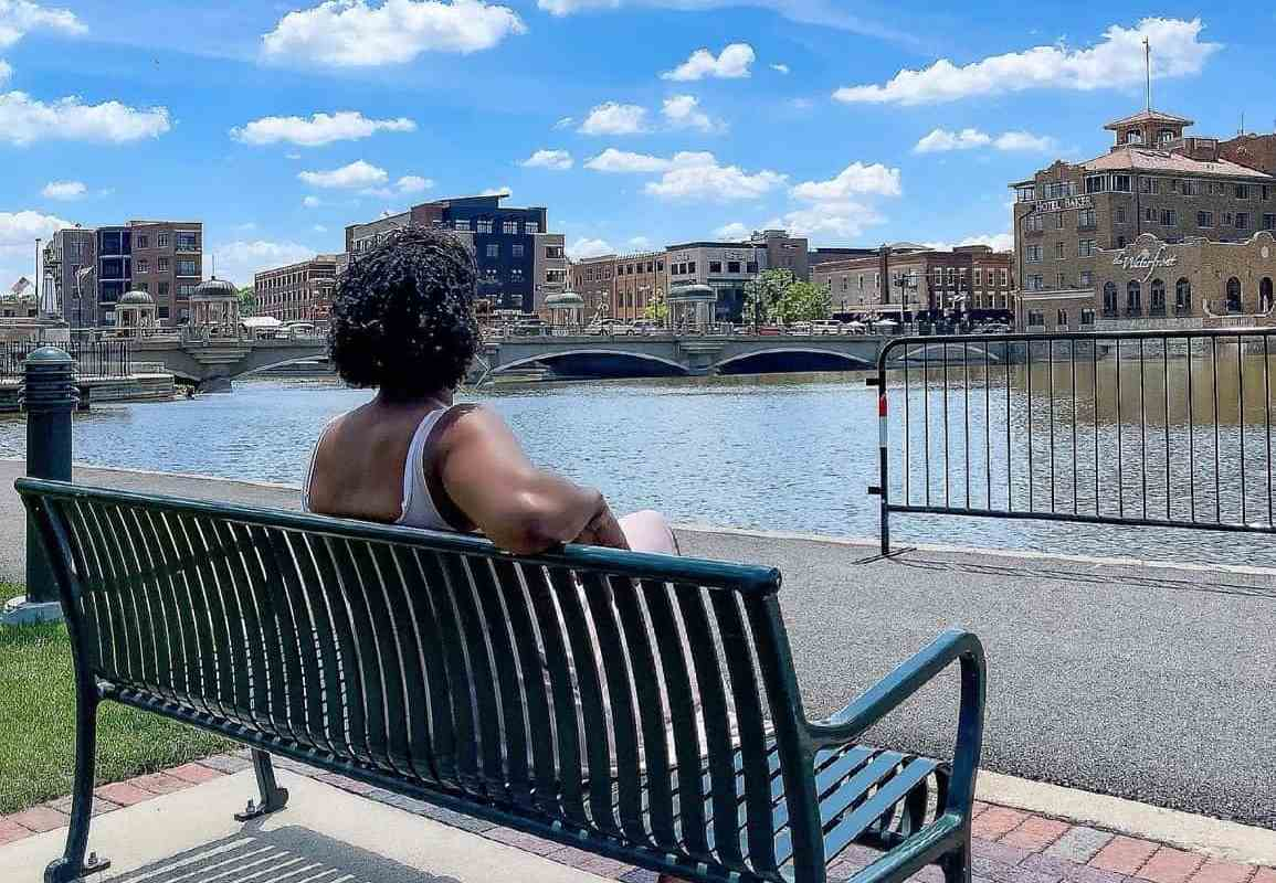 woman sitting on park bench on the Fox River