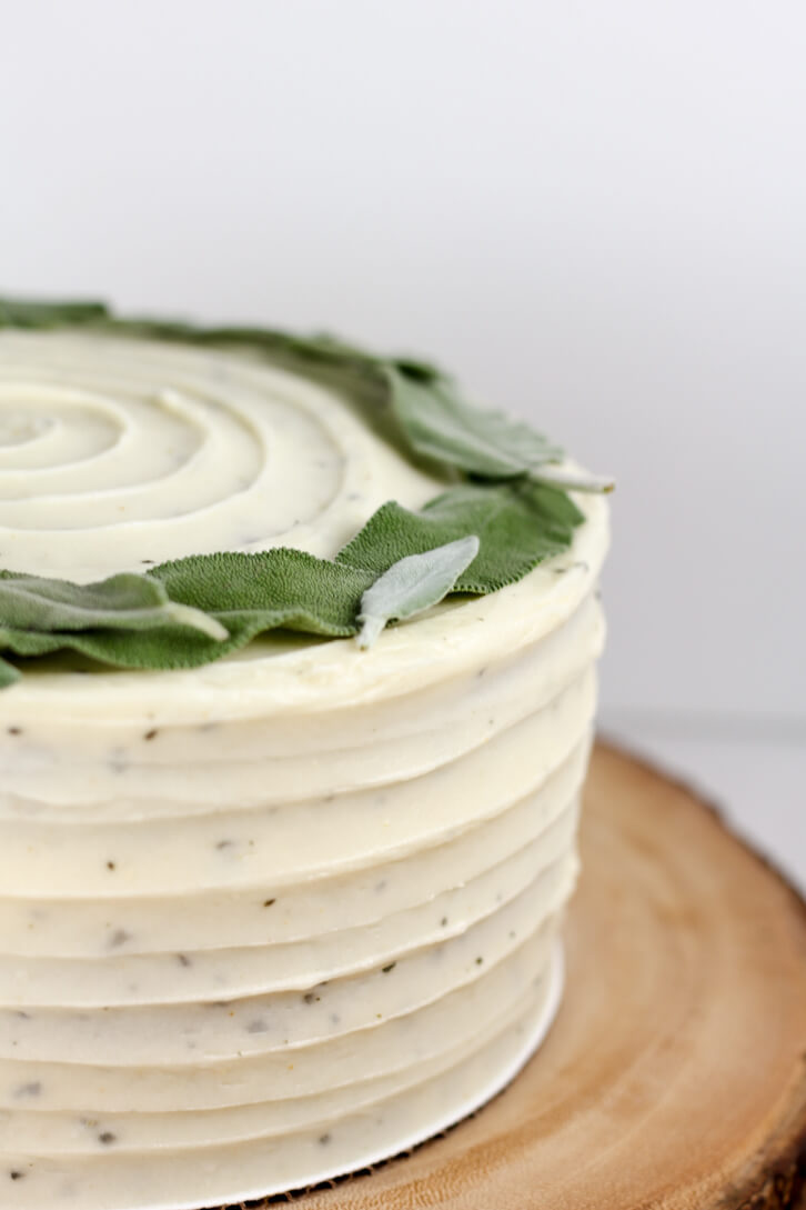 A crown of pale green sage leaves on top of a sweet potato cake with brown butter sage frosting