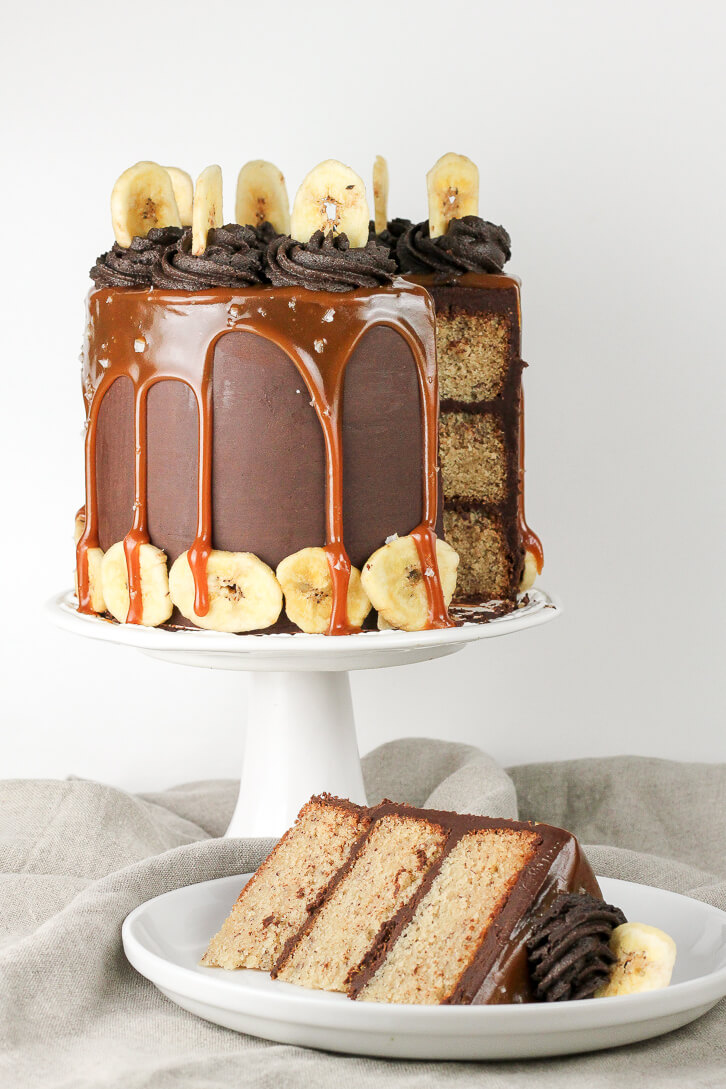 A slice of a triple layer banana cake with dark chocolate ganache frosting