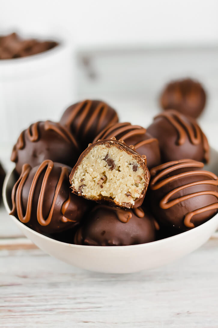 A bowl full of chocolate chip cookie dough truffles - this edible cookie dough is made with oat flour and will satisfy all your cookie dough cravings without the eggs.