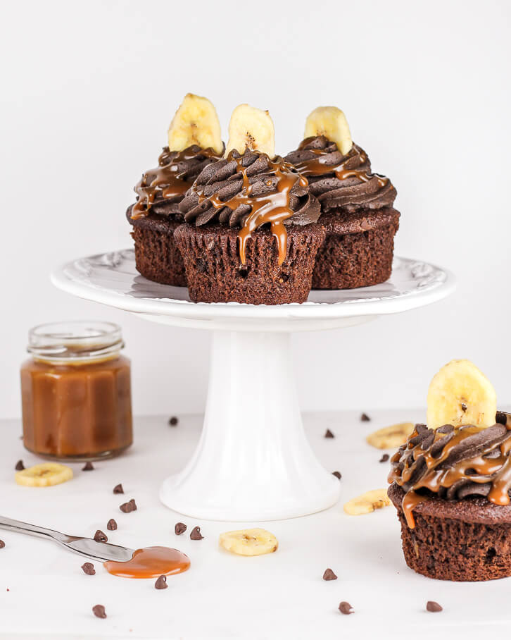 A cake stand is perfect for showing off these triple chocolate banana cupcakes topped with dark chocolate buttercream and homemade caramel sauce