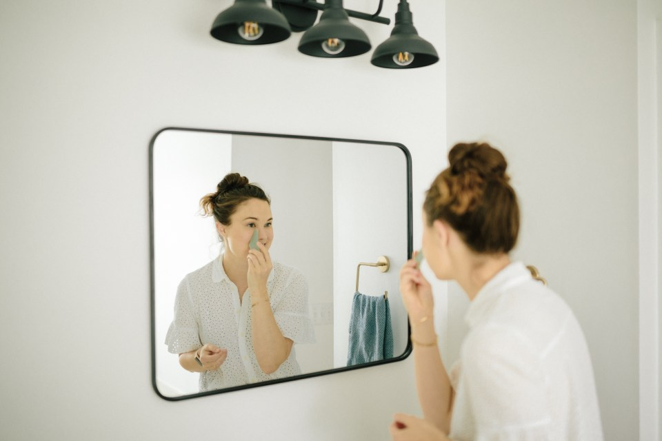 Carolina showing gua sha techniques in the mirror.