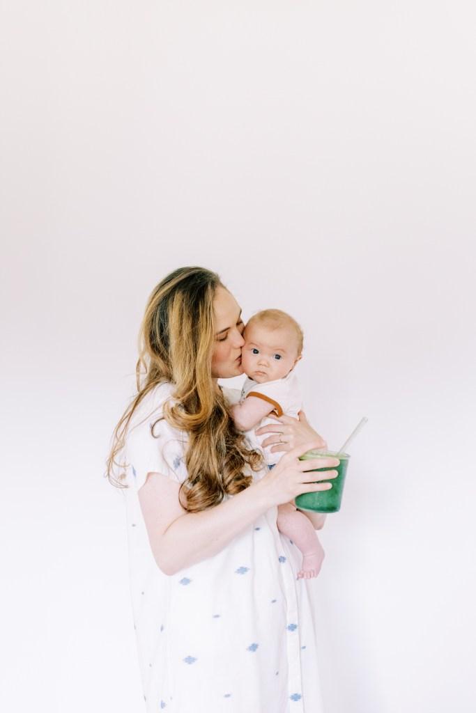 Caroline holding her newborn and Majka postpartum nutrition replenisher.