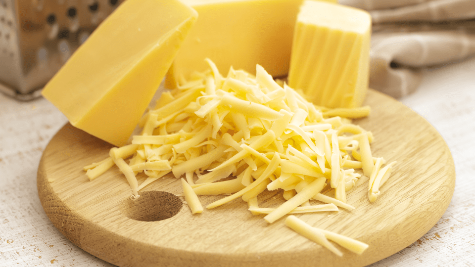 shredded cheese and block cheese on a cutting board