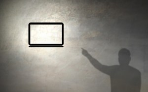 image of man's shadow pointing at laptop
