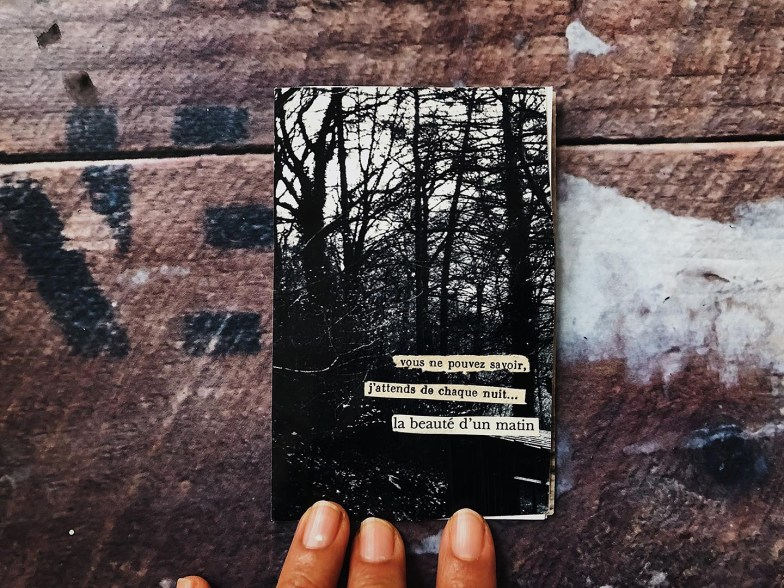 A small zine depicting a forest with cut out poetry