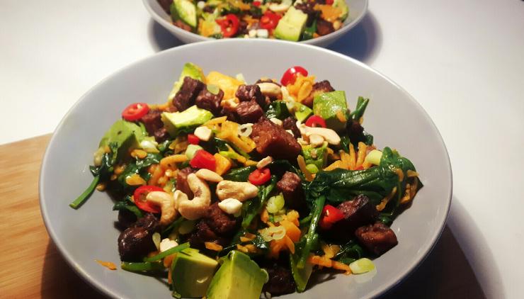 vegetarische spinazie-pompoensalade met avocado en tempeh