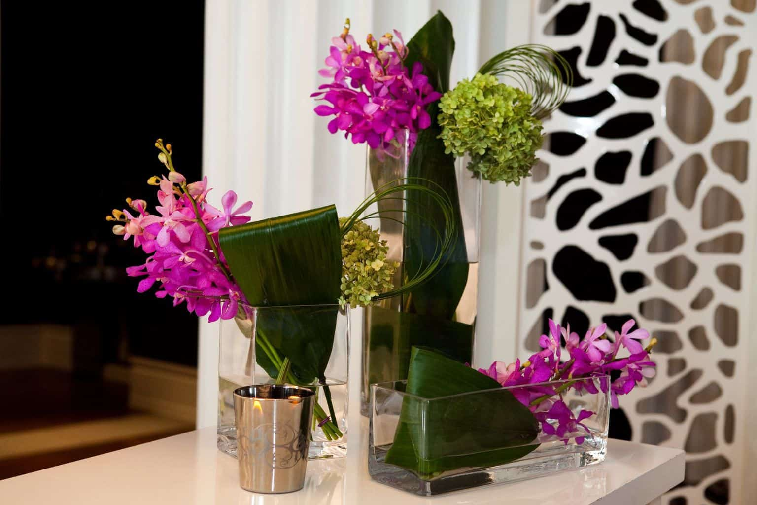 A collection of vases with orchids and green hydrangea