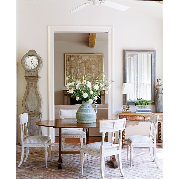 Gerrie Bremermann is known for her affinity for a white palette and her love of antiques, particularly French, such as this 19th-century wine table that mingles with Swedish chairs and clock. | Photo by Tria Giovan