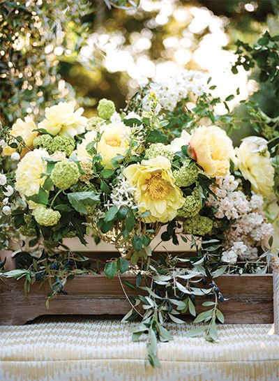 A romantic mix of clematis, garden roses, and olive branches captures the garden-inspired theme of the workshop.