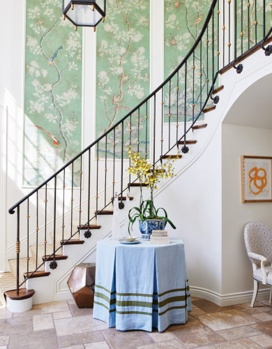 Garden-inspired chinoiserie panels decorate the entryway of a California home. A pale-blue tableskirt with olive trim combines the colors of sky and garden.