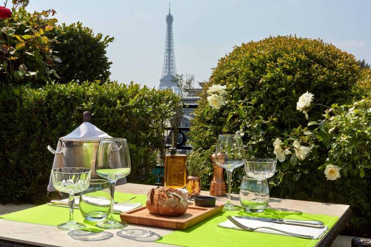 A rooftop cafe table surrounded flowering and green shrubs, with a view of the Eiffel Tower in the distance
