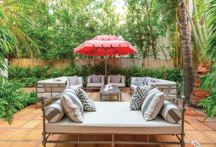 Photo of a terra cotta tile patio with outdoor seating surrounding a coffee table shaded by a red umbrella. Gray-and-white throw pillows feature stripes and a Greek key pattern.