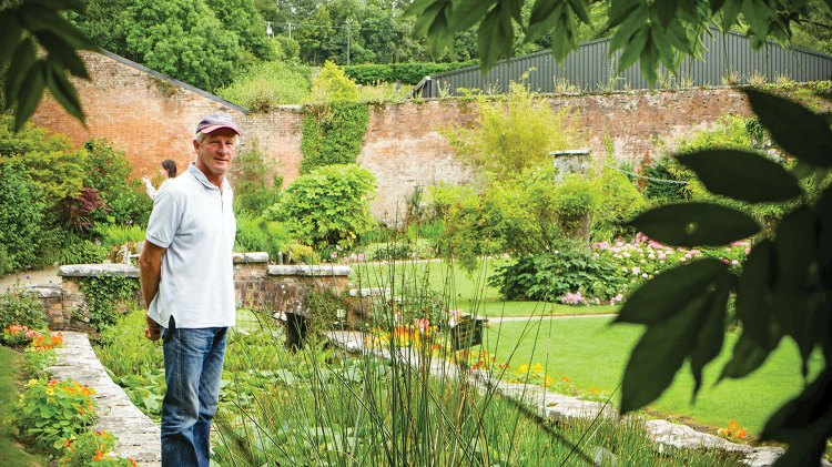 Wearing a baseball cap, polo shirt and jeans, Arthur Shackleton stands on the stone edge of a plant filled garden pond at at Dromoland Castle, holding his hands behind his back.
