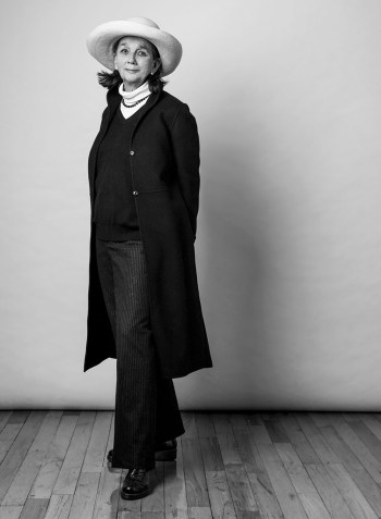 In a black-and-white photo, Cecily Pennoyer wears a brimmed light-colored hat, white turtleneck with a dark beaded neckless, and a dark sweater, pants and knee-length coat.