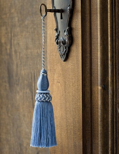 blue decorative tassel hanging from a key in a natural-finish wood door