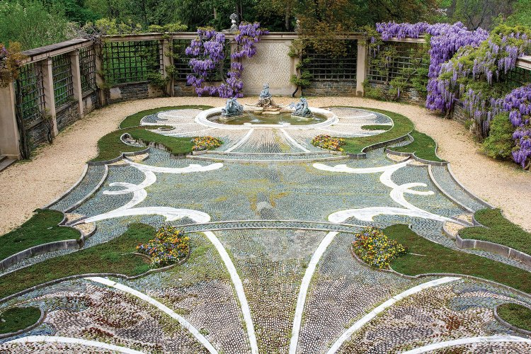 Intricate pebble hardscape featuring curvy inlays of grass and plantings, anchored by a fountain at one end, surrounded by walls designed by Beatrix Farrand