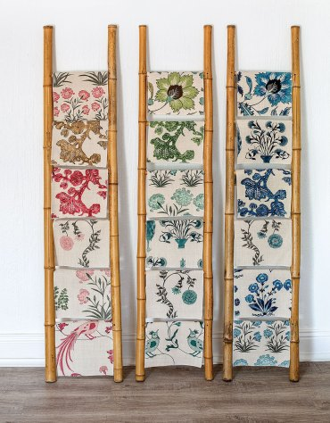Assorted pink, green and blue botanical print textiles, designed by Debby Tenquist of Botanica Trading, hang on bamboo display racks