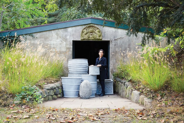 Newman stands in the doorway of a stuccoed shed with a collection of large planters. Trees and tall grasses surround the area.