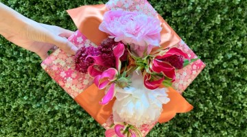 If you're looking for creative gift wrapping ideas, try re-creating this wrapped gift box with fresh flowers tucked into the ribbon