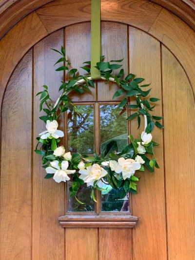 Floral hoop hung on a natural wood front door