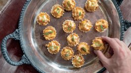 A hand grabs a Crawfish Cardinale Tart, a recipe by Julia Reed, from the tray