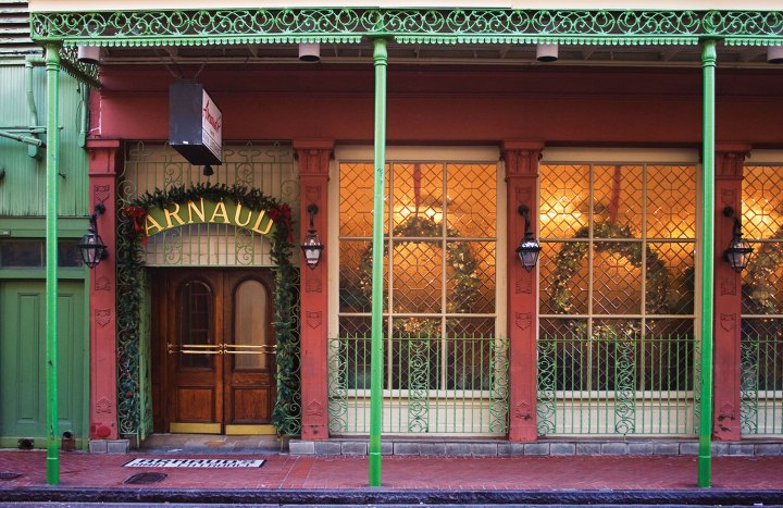 Red exterior of Arnaud's Restaurant in the French Quarter. It has a classic New Orleans iron balcony that's painted a bright green, as well as leaded windows