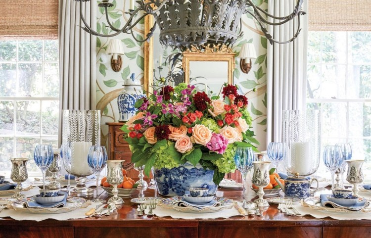 A large wooden table graciously set with blue-and-white china, blue-tinted crystal goblets, silver goblets, two large glass hurricanes holding a large candle each, and—at the center—a large blue-and-white china tureen filled with a flower arrangement of peach, pink, green, coral, and burgundy blooms.
