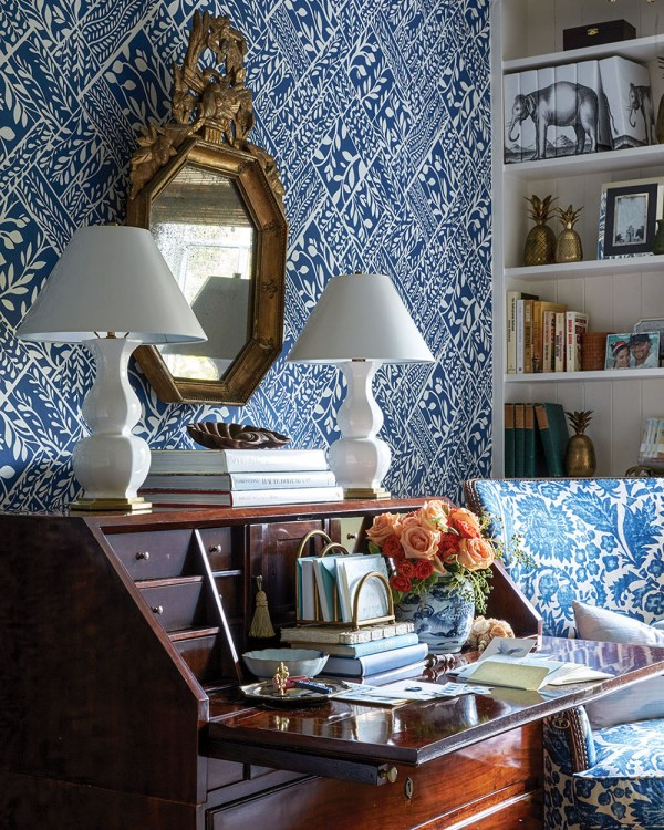 A blue-and-white wallpapered room with a matching chair, a wooden secretary desk with hinged drop-down top, two white lamps, and a gilded antique mirror. White built-in bookshelves hold books, brass pineapples, framed photos, and a set of books whose covers all together form a pen-and-ink-style illustration of picture of an elephant.