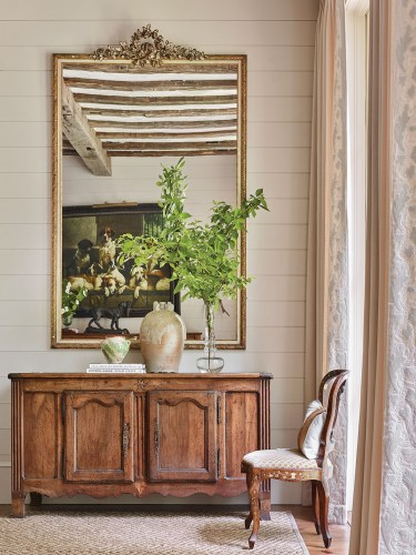 Other chic mountain house decorating ideas from this scene include a non-fussy French country-style natural wood console beneath the mirror. One top of the console are two rustic pottery jugs—one large and one small—a small stack of books, and a simple arrangement of green branches in a clear glass vase with an interesting shape. An antique French chair sits by the window, framed by soft white floor-to-ceiling curtains in a white-on-white, raised botanical print