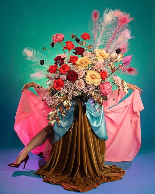 A woman's leg and arms peek out behind layers of skirts and a vibrant flower arrangement of red, purple, and yellow blooms. The scene is a collaboration of Marisa Basquez-White's floral design and Amanda Rowan's photography