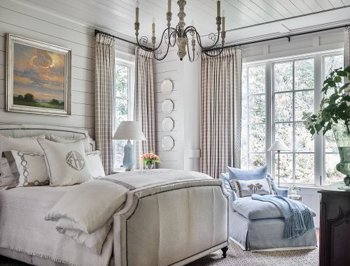 The master bedroom's white-on-white palette gains depth from layers of contrasting textures, including rough shiplap walls, smooth porcelain plates, and the coarse hair-on-hide bed. A blue chaise with matching throw and a glazed lamp add a pop of light blue, while a landscape painting featuring a morning sky also breaks up the neutral palette.