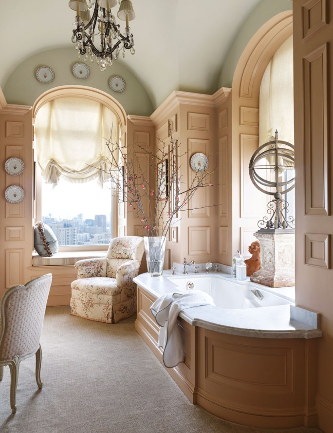 Other luxury bathroom decor shown hear includes a crystal chandelier, a cushioned window seat, tall arched windows and ceilings, and comfortable chairs.