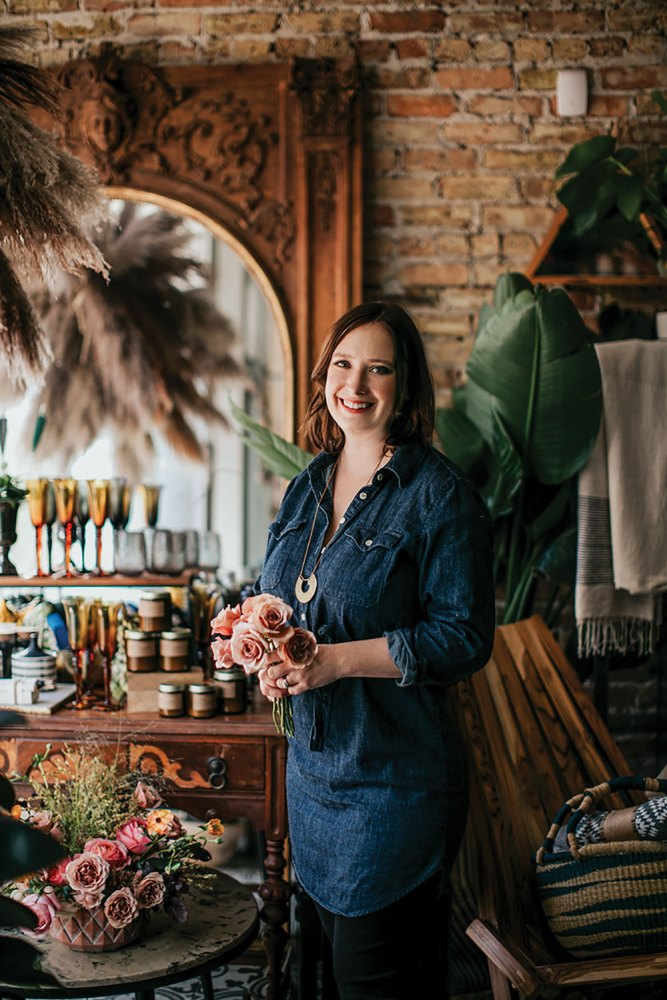 Portrait of floral designer Kelly Marie Thompson in her shop, Fleur, in Chicago. She wears a denim tunic and dark pants, and holds a small bouquet of roses. She's surrounded by flowers, grasses, large tropical leaves, and the antiques that fill the shop's exposed brick frame.