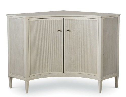 white corner cabinet with a pair of concave curved doors with a linear pattern