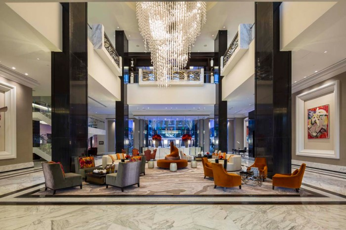 The Post Oak Hotel's two-story lobby features a massive chandelier dripping in crystals. With marble floors, dramatic black accents, and modern art and furniture, the contemporary interior nods to 1920s Art Deco style.