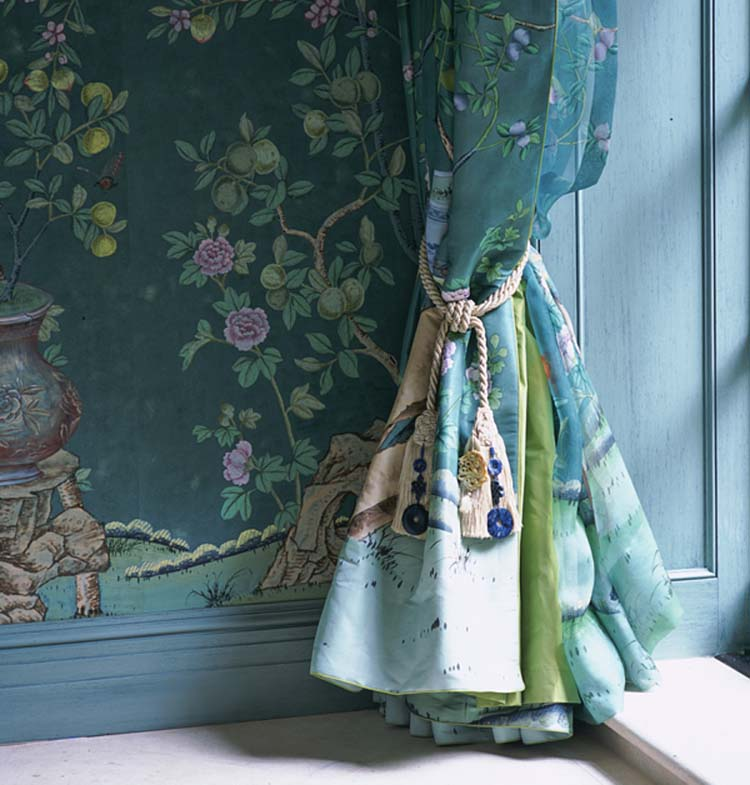 Close up of a blue-green floral curtain tied back with a tassel, which is complemented by the similarly hued wallpaper