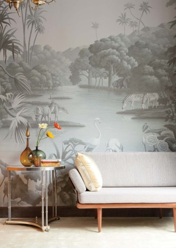 De Gournay wallpaper in a gray color palette featuring birds, zebras, and other African animals gathered around a tree-lined watering hole